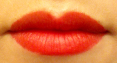 Fluorescent light lip swatch of Revlon Colorstay Ultimate Liquid Lipstick in Top Tomato